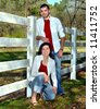 Brother and sister pose besides white fence.  Both have on jeans, white shirt and red shirt.  Smiling. - stock photo