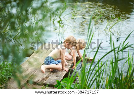 Brother and sister sitting on the river bank. Beautiful children playing with water on the bridge. Boy and girl near a pond in the summer.