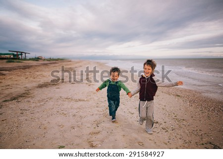 brothers running on beach holding hands smiling