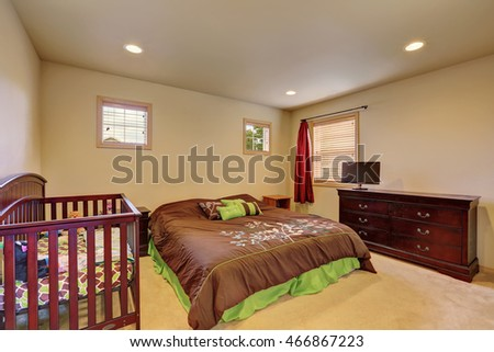 Brown bedroom with crib and vintage chest of drawers. Northwest, USA