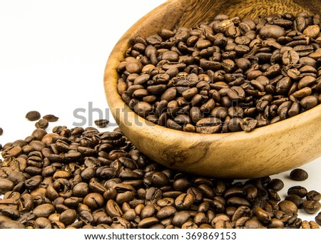 Brown coffee beans isolated on white background / roasted coffee beans, can be used as a background / wooded plate or cup