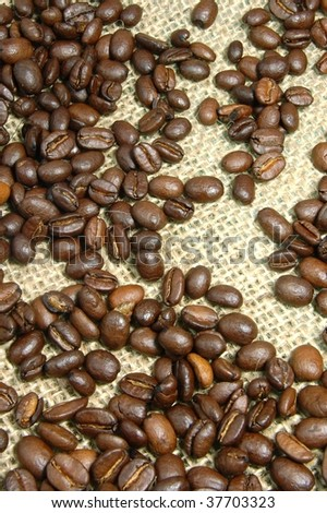 brown coffee beans on burlap which can be use as background.