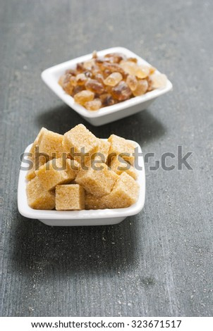 brown cubes and rock sugar on white square dishes, dark wood table