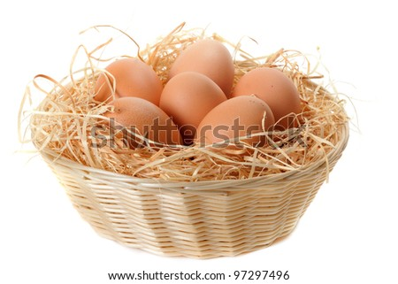 Brown eggs at hay in the basket on white