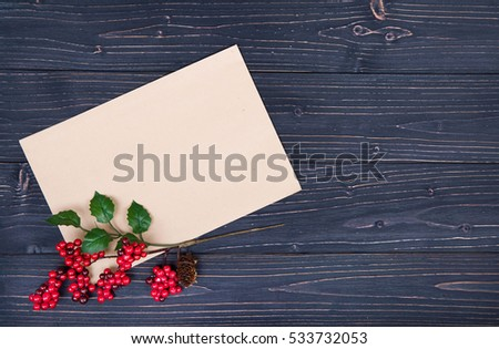 brown envelop and christmas holly on  wooden table