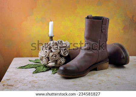 Brown genuine haft boots on grunge with dry flowers and candles still life art photography