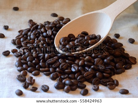 Brown roasted coffee beans and wooden spoon on piece of linen textile -food background