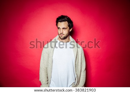 Brunette brown haired man with beard and white t-shirt and red hoody in front of beige studio backdrop