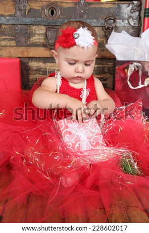 Brunette christmas baby girl wearing a long red tulle dress
