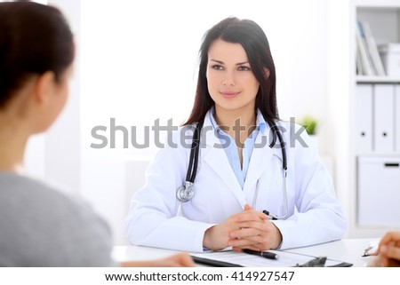 Brunette female doctor talking to patient in the hospital