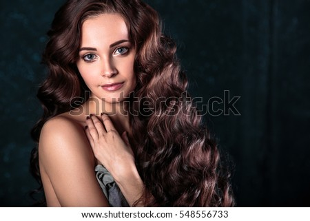 Brunette girl with long and shiny wavy hair . Beautiful model with curly hairstyle and natural makeup.