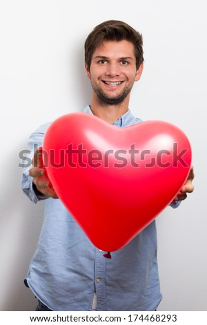 Brunette man wearing a blue shirt and holding a red heart balloon