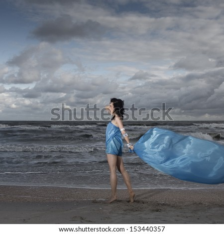 Brunette model standing on sea shore with long flag material