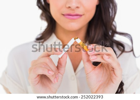Brunette snapping her cigarette on white background