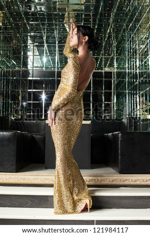Brunette woman in gold dress