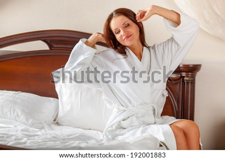 brunette woman in white bathrobe waking up