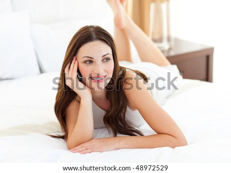 Brunette woman on phone lying on bed at home