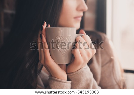 Brunette woman 20-24 year old holding ceramic cup of tea closeup. Looking at window. Good morning. Selective focus. 20s.