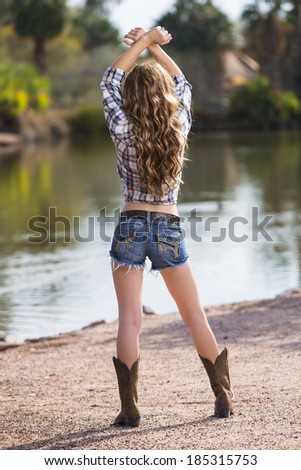Brunette young model posing in cowboy outfit