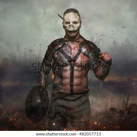 Brutal artistic male in the skull mask holds sword in the dust battelfield background.