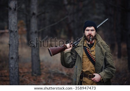 brutal hunter, bearded man in warm hat with a gun in his hand, a knife a backpack and smoking pipe in the wild forest in the autumn