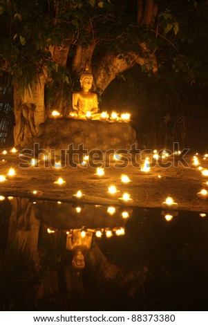 Buddha statue reflect on water with candles fire lighting