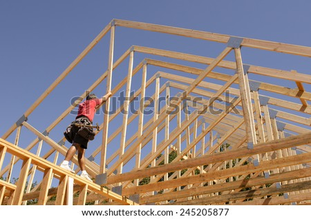 Building contractor carpenter placing new home wood engineered trusses on a residential construction site