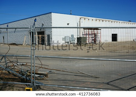 building in construction site surrounded by iron fence
