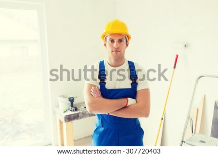 building, repair and people concept - builder in hardhat and overall with working tools indoors