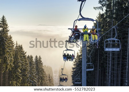 Bukovel, Ukraine, December 2016 - Happy young skiers with action camera rising up of a chairlift above the clouds in winter resort
