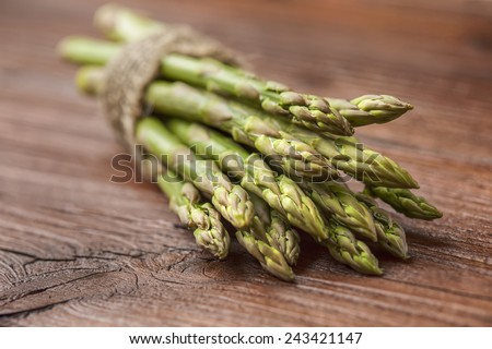 bunch of asparagus stems on brown wooden table. One of 5 greens a day