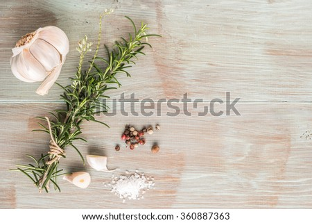 Bunch of fresh of garden rosemary on wooden table, rustic style, fresh organic herbs with salt, chili and garlic. Top view with copy space