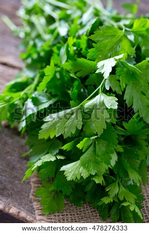 bunch of fresh parsley leafs on wooden surface