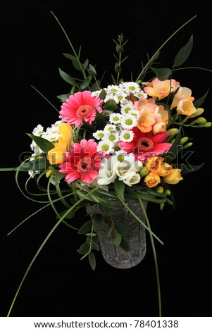 Bunch of many different flowers in crystal cut vase on black background