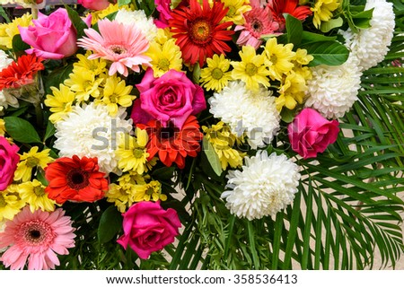 Bunch of vivid flowers, flower bouquets including fuchsia roses, white chrysanthemums, pinke gerberas, and red marguerite daisies.
