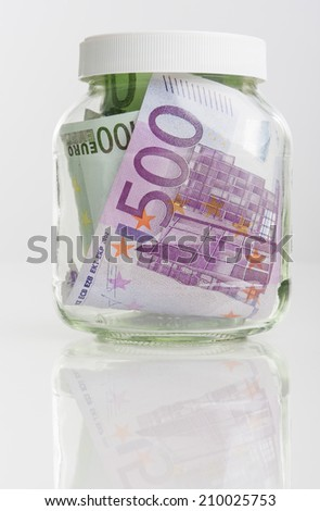 Bundle of European Currency Banknotes Put in Jar Isolated Over White Background