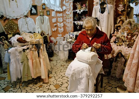 BURANO, ITALY - MARCH 089, 2008: unidentified woman sit in her little shop and sew on March 08, 2008, in Burano, Italy
