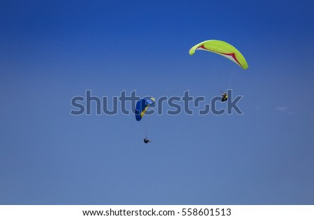 Burgas - July 29: Two paraglider - yellow green and blue flying against the blue sky and airplane in the distance on July 29, 2016, Burgas, Bulgaria
