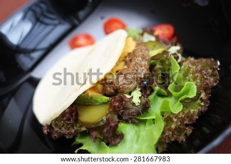 Burger with meat and baked vegetables on plate