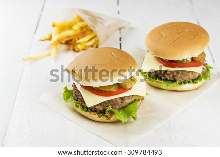 Burgers and french fries on a white wooden background