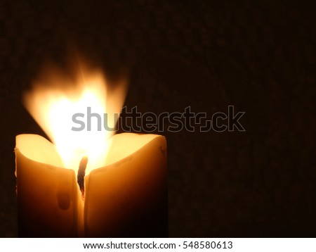 Burning Candle Against Dark Background with Flame Blowing - Photograph of a light colored candle burning against a dark background and the flame blowing wildly in a breeze.