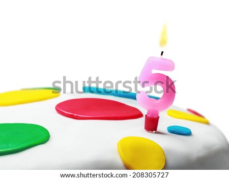 Burning candle with the number five on a birthday cake. birthday greetings