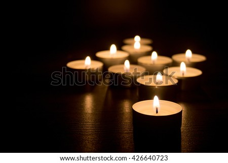 Burning candles on a black background . Selective focus