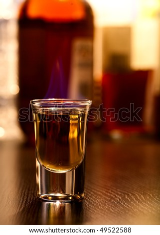 Burning cocktail in shot glass on a table, shallow focus
