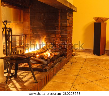 Burning fire wood in fireplace. Home interior indoor.