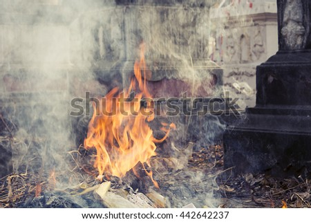 Burning Silver and gold paper to worship ancestor in Chinese culture, the Qingming Festival at graveyard Cemetery