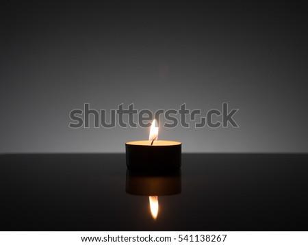 Burning tea light on reflective glass surface. & Burning Tea Light On Reflective Glass Stock Photo 541138192 ... azcodes.com