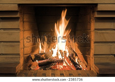 Burning wood logs in fireplace during Christmas time.