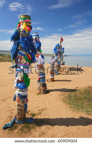 Buryat traditional pagan holy poles by the Lake Baikal. A row of vertical logs with colored rags