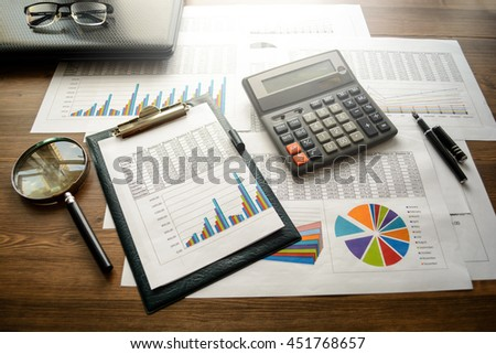 Business accessories (notebook, calculator, planchette, tablet, fountain pen, glasses) and graphics, tables, charts on white sheets on office desk. Soft focus, lights effects.